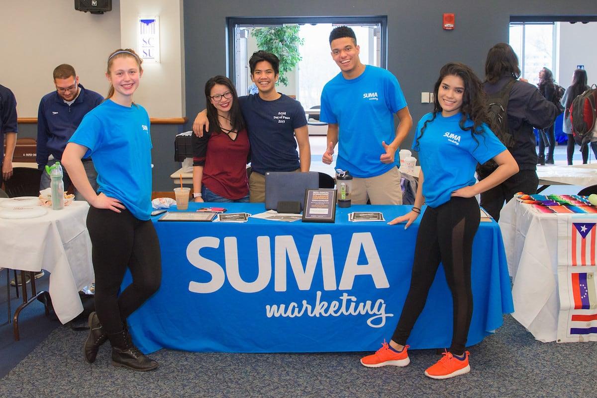 Students around SUMA Marketing table at the club fair