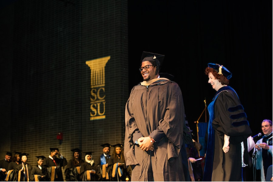 A student in cap and gown at the podium during graduation ceremony