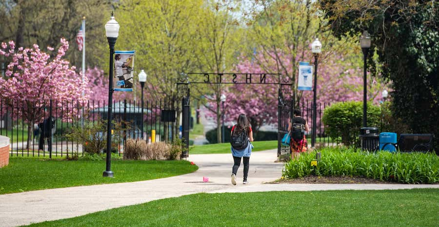 campus scene of student walking through Founder's Gate
