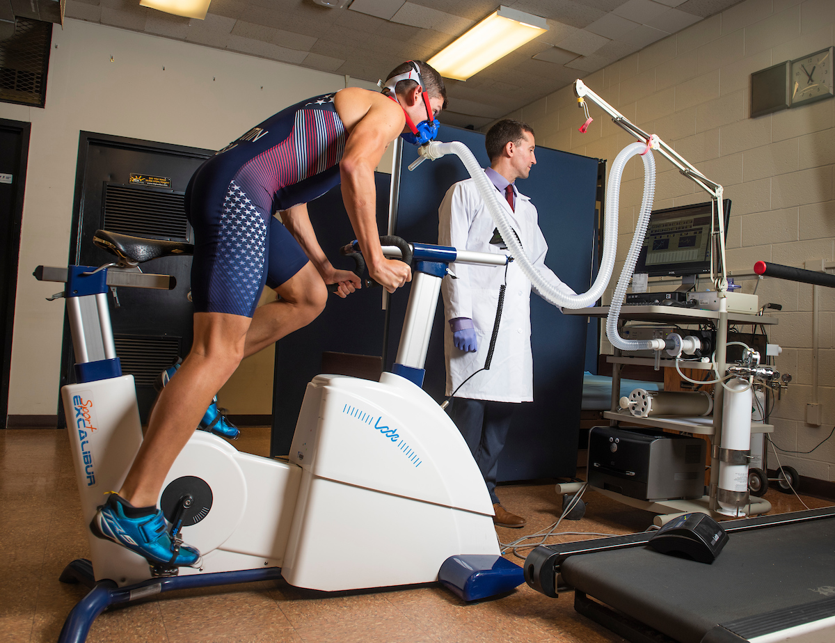 Athlete on a treadmill hooked up to a machine, and a scientist observing the data