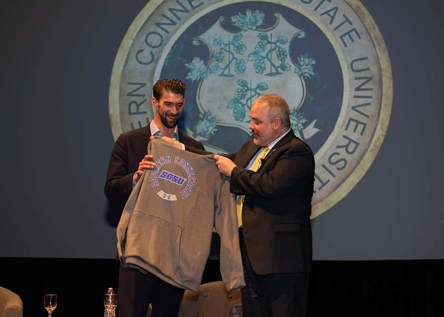 President Joe Bertolino presents Michael Phelps with a Southern sweatshirt