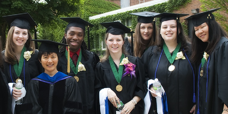 A group of students and faculty in graduation cap and gown