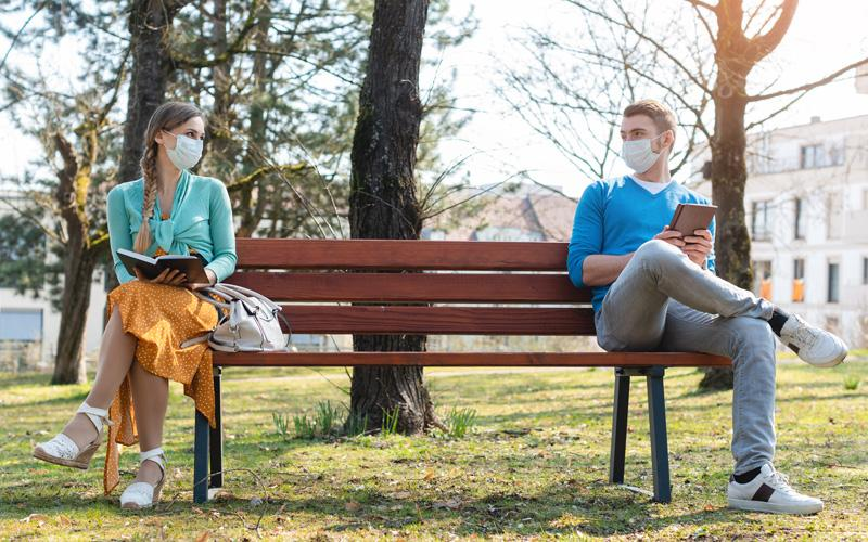 two people wearing face masks sit far apart on a park bench