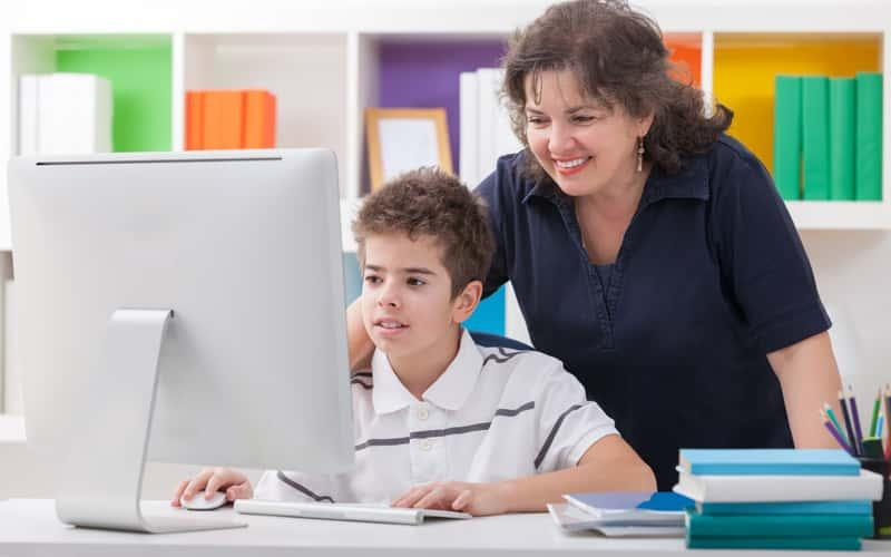 a mother looks over her young son's shoulder as he works on a computer