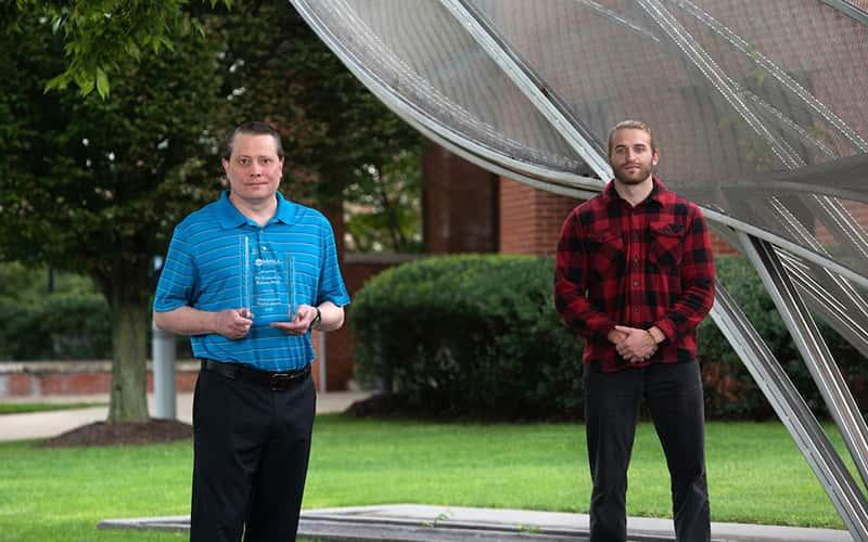 ken walters and paul mckee stand in front of the campus wave sculpture