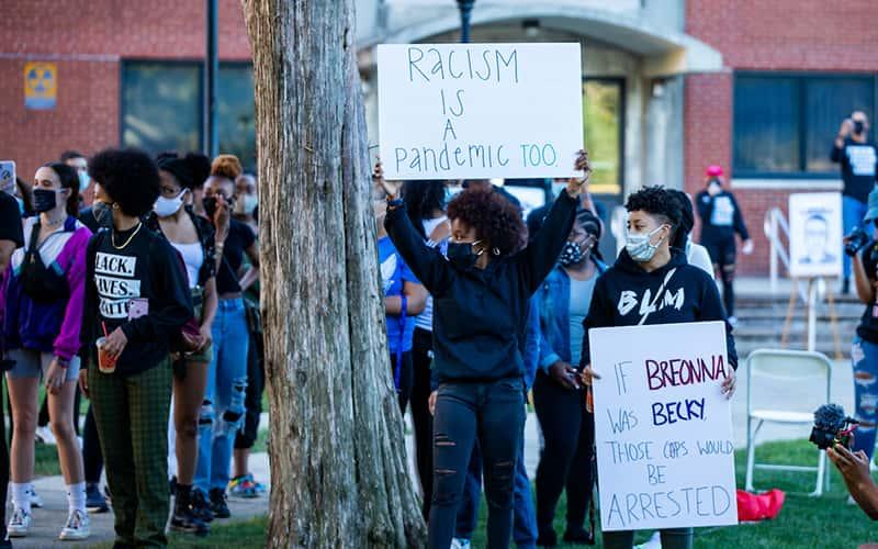 students hold signs protesting racial injustice