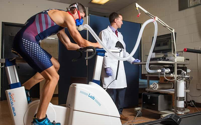 a male riding a stationary bike is monitored by a professor in a white coat