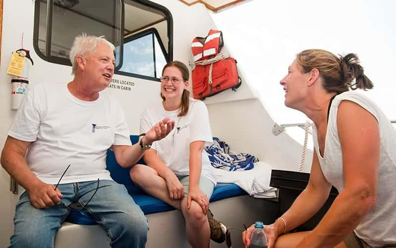 Jim Tait and two students talk together on a boat