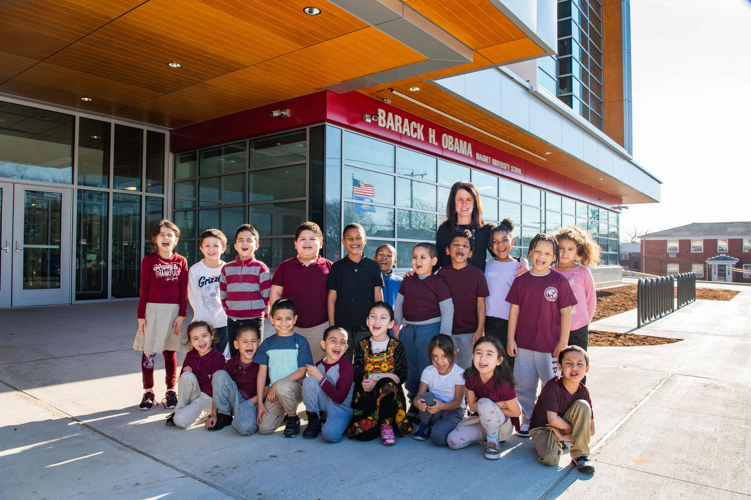 a group of young students with their school principal stand in front of the Obama School