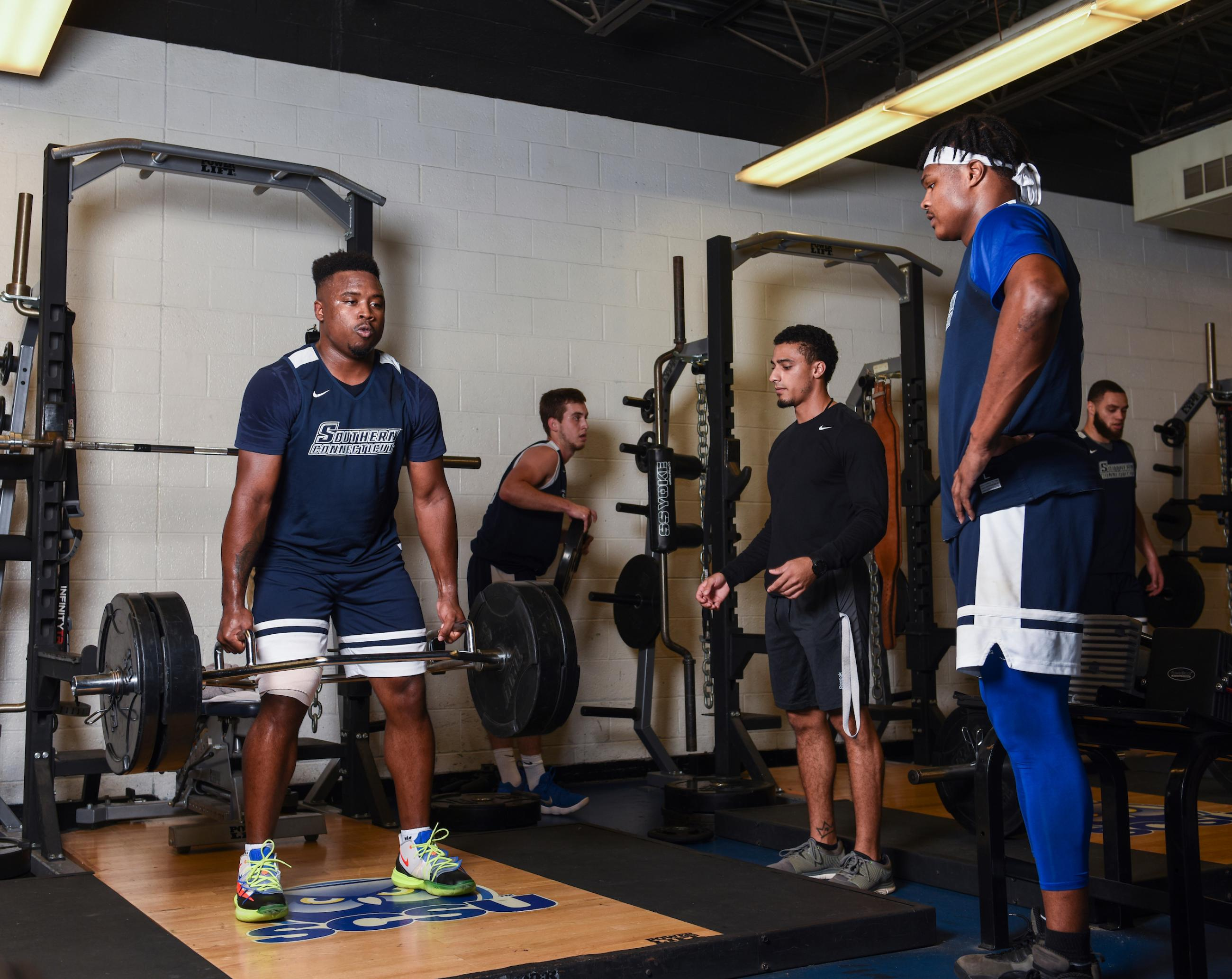 """An athlete lifting weights and students observing"""