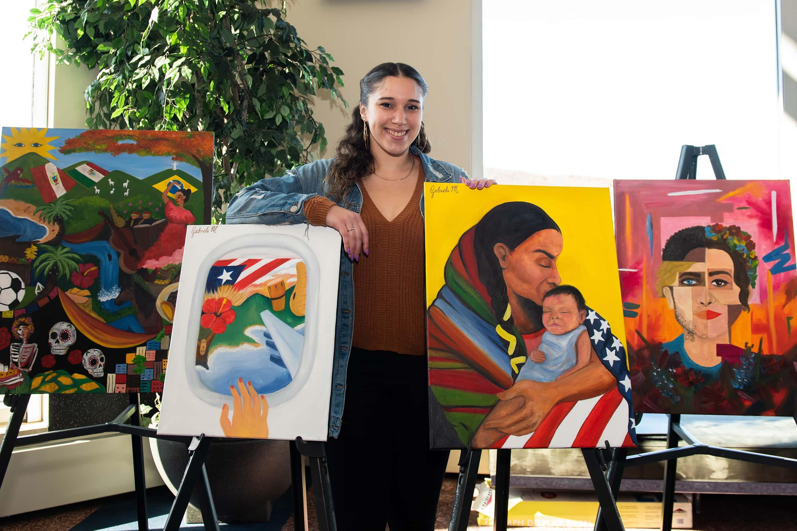 a female student displays four paintings she made