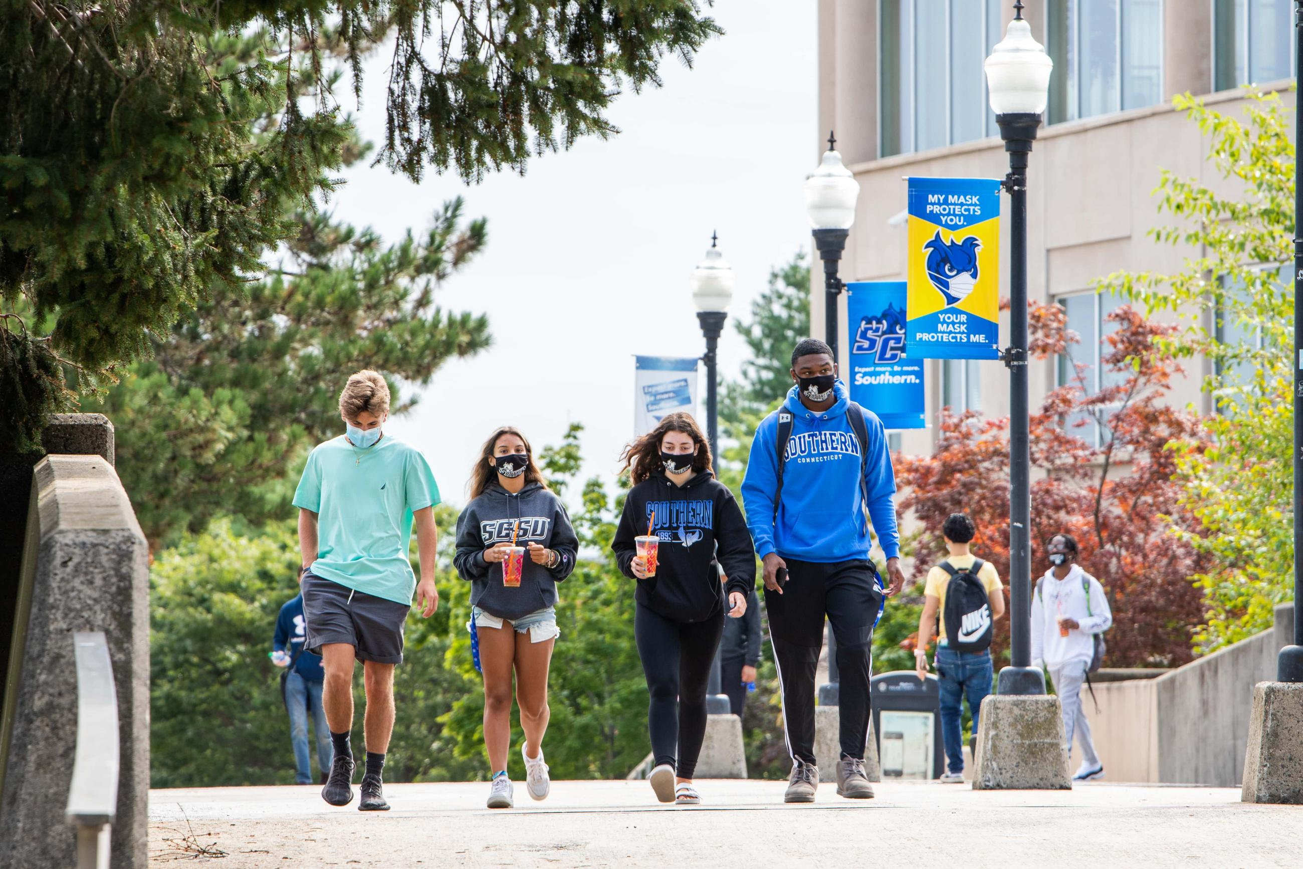 students walk on campus, wearing face masks