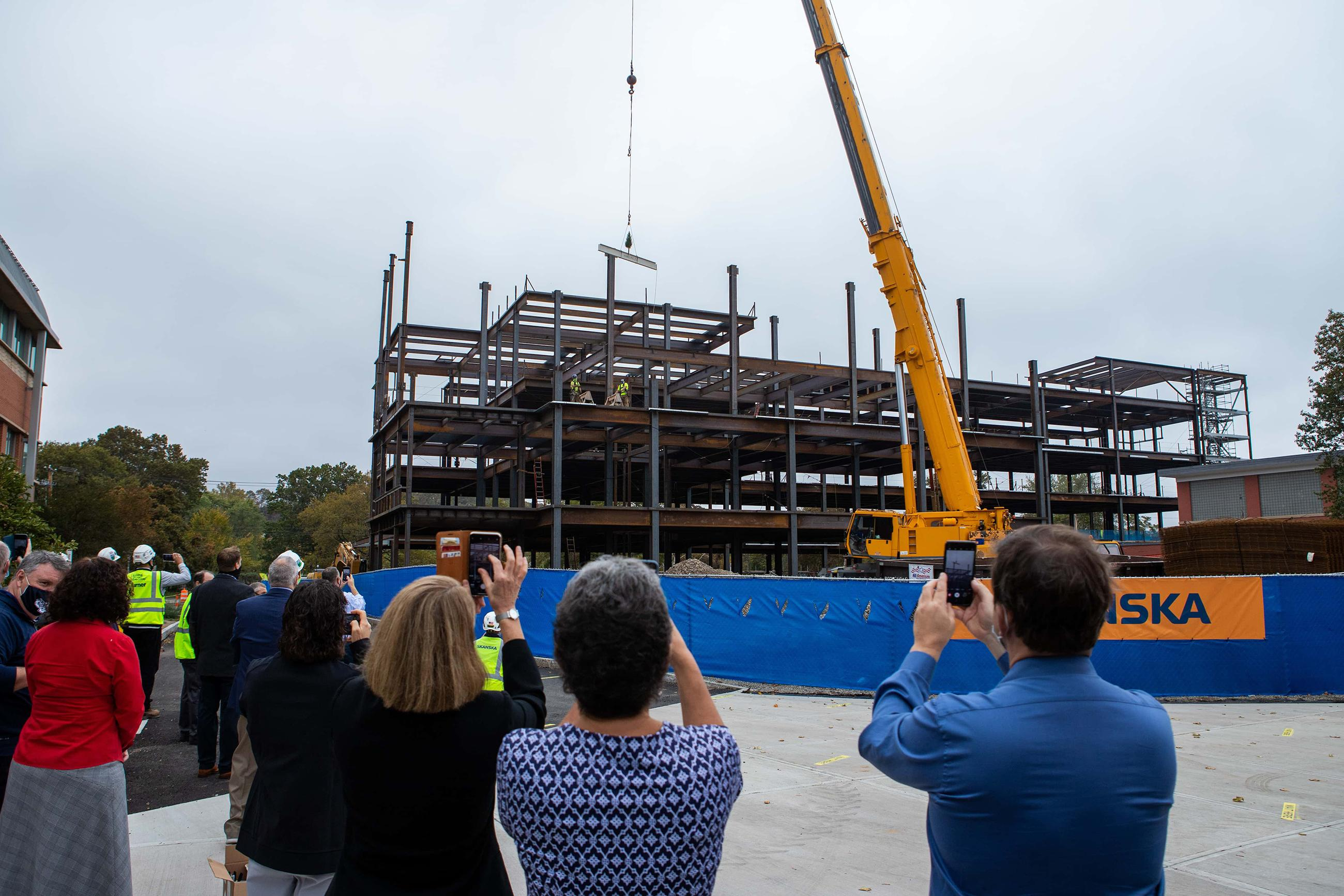 faculty and staff watch and take photos as the final beam is put into place on the new health and human services building on campus